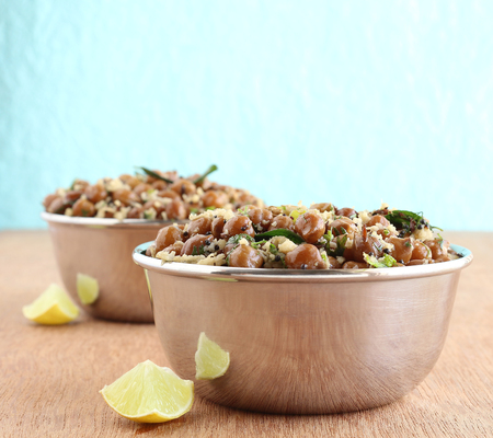 gratings: Indian food brown chickpea curry, a healthy vegetarian, traditional and popular side dish, in steel bowls.. Stock Photo