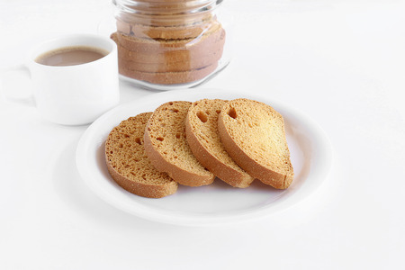 rusk: Healthy snack rusk, made from whole-wheat flour, in a plate and a cup of coffee and a bottle containing rusks.