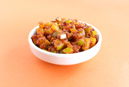 Raw mango pickle, an Indian traditional side dish, in a bowl.
