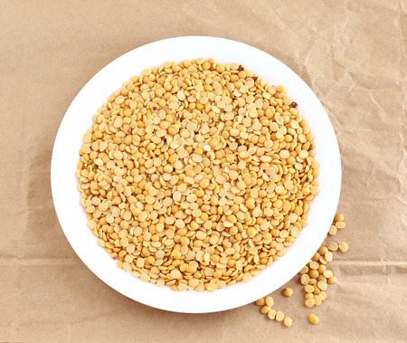 pigeon pea: Toor dal, also known as split pigeon pea, rich in proteins, in a plate on a crumpled brown paper background.
