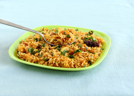 Indian food tamarind rice, which is a vegetarian, traditional, popular and south Indian rice dish, on a steel spoon.