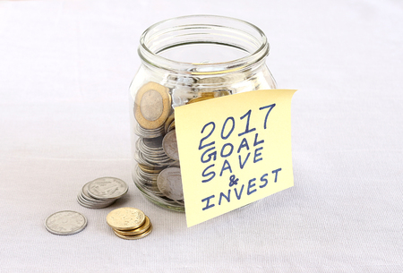 long term goal: Concept of financial goal for the year 2017, highlighted with a handwritten note posted on a bottle of Indian currency coins.
