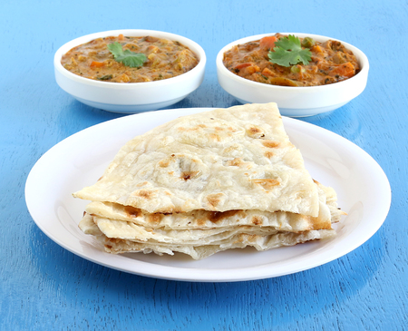 Indian food naan, a type of traditional and popular bread, and vegetable curries. Stock Photo