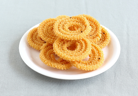 Chakli, also known as murukku, which is a south Indian traditional, popular and vegetarian snack, on a plate.