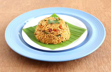South Indian traditional and popular vegetarian rice dish, puliyogare, made from rice and a paste containing tamarind and other ingredients.