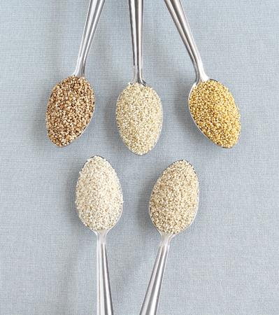 Healthy food millets in steel spoons.