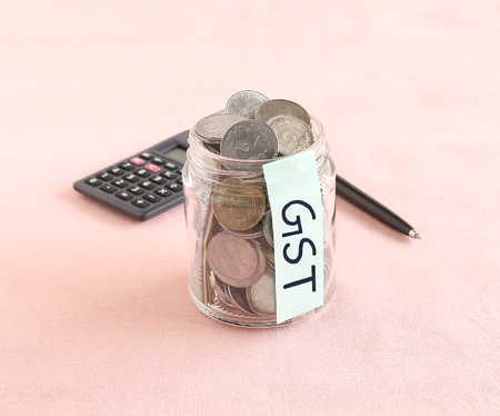 GST or goods and services tax concept, highlighted with Indian rupee coins in a bottle and handwritten text on a label on the bottle.