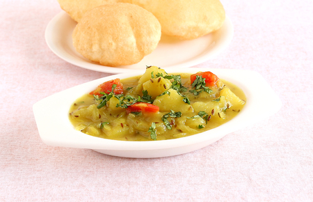 Aloo sabzi, or potato curry, is an Indian vegetarian food, which is used as a side dish for items like poori or Indian fried bread.