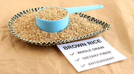 Brown rice, which is a whole grain and healthy food, in a measuring cup, with a note of some of its benefits.