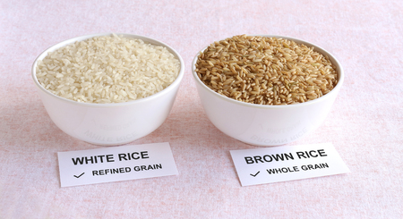 Brown rice, which is a whole grain and healthy food, and white rice, which is a refined grain, in a bowl.