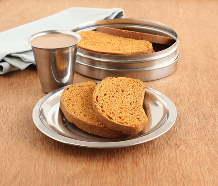 teething: Rusk, a popular, crunchy and crispy biscuit, and tea, on a plate on a wooden background.