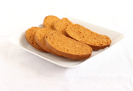 teething: Rusk, a popular, crunchy and crispy biscuit, and tea, on a plate.