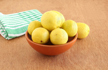 Lemons in an earthen bowl on a wooden background. Stock Photo