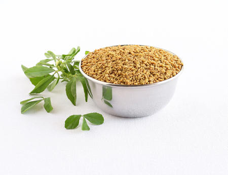 Methi or fenugreek seeds in a steel bowl and in the background are methi leaves. Stock Photo