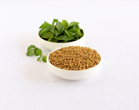Methi or fenugreek seeds in a bowl and in the background is a bowl of methi leaves.