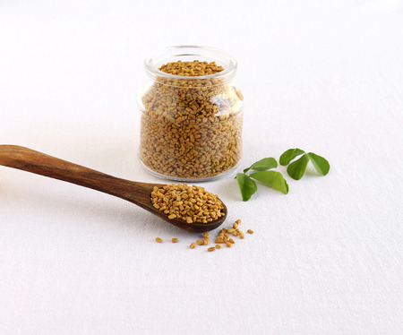 Methi or fenugreek seeds in a wooden spoon and in the background is a bottle of the same seeds and next to the bottle are methi leaves.