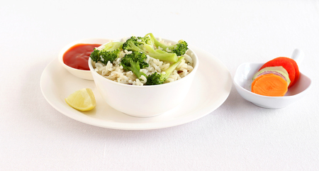 Broccoli rice, a healthy vegetarian food, with tomato ketchup as a side dish and salad. Stock Photo