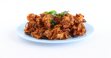 Pakora or pakoda, a traditional and popular Indian vegetarian snack, in a tray.