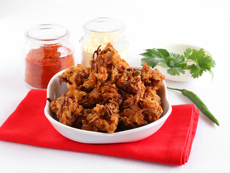 Pakora or pakoda, a traditional and popular Indian vegetarian snack, with some of its ingredients like besan flour and chili powder.