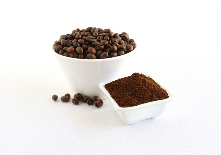 Coffee beans and powder, which is freshly ground, in bowls.
