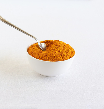 Turmeric powder, or haldi, traditional and popular ingredient used in many Indian dishes, scooped with a steel spoon from a white ceramic bowl. 写真素材 - 96141726