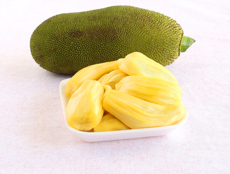 Jackfruit arils or bulbs heap in a tray, and in the background is a jackfruit. 스톡 콘텐츠