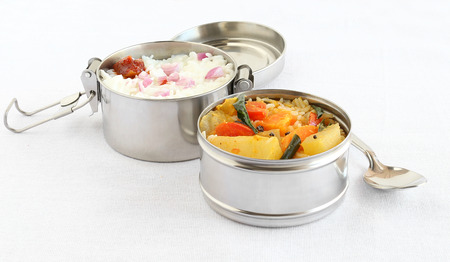 Healthy south Indian vegetarian lunch in two boxes of a lunchbox, with rice and sambar, a semi-liquid food made from lentils and vegetables, in one box, and curd rice in another box.