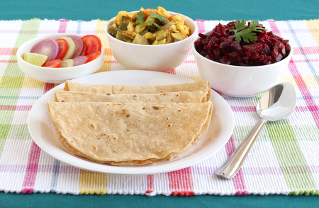 Chapati, also known as Indian flat bread, homemade without oil, India's traditional and popular vegetarian food with vegetable and beetroot curry and salad as side dishes on a table mat. Banque d'images