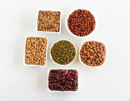 Legumes, healthy food and organic type, including garbanzo, kidney beans, mung and black-eyed peas in bowls, are said to be rich in, among others, fiber and proteins.