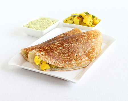 Masala dosa, a south Indian vegetarian, traditional and popular crepe, known globally, with coconut chutney and potato and onion curry, in a tray. Stock Photo