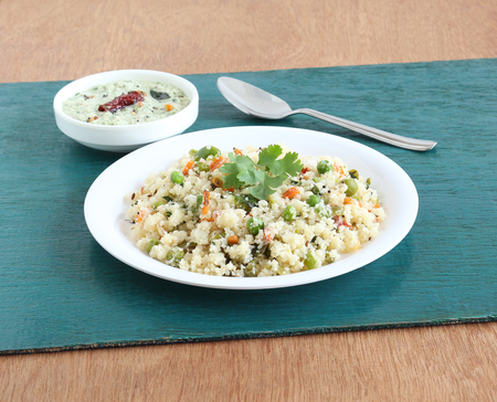 Rice upma, a south Indian vegetarian breakfast made from shredded rice and vegetables, with coconut chutney as a side dish. Stock Photo - 100620063