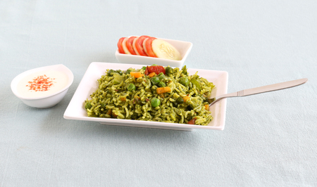 Palak rice, biryani or pilaf, which is made from spinach and vegetables is an Indian vegetarian healthy food, with yogurt and tomato-cucumber salad.
