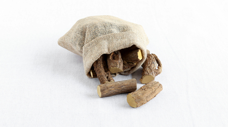 Licorice roots or sweet roots, a sweetener used in candies and beverages and that are said to be a natural medicine for health issues like gastrointestinal problems, in a sack. Imagens