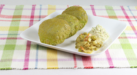 Palak poori, made from spinach puree and wheat flour dough is a popular Indian vegetarian breakfast, on a plate with vegetable curry and coconut chutney as side dishes. Stock Photo