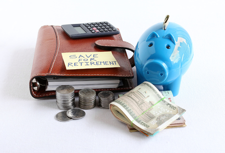 Save funds for retirement concept highlighted by handwritten text on a paper attached to a diary and Indian rupees and coins stack, a calculator and a piggy bank.