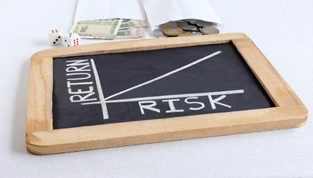 Concept de relation de risque et de retour, mis en évidence par un texte manuscrit et un graphique dessiné à la main sur un tableau noir, des roupies indiennes et des pièces de monnaie et des dés.