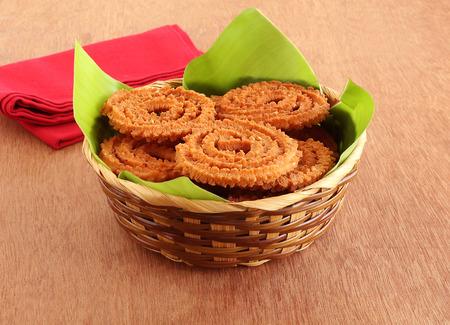 Chakli lub chakkuli to tradycyjna, popularna, wegetariańska i pyszna indyjska pikantna przekąska, zwykle przygotowywana podczas niektórych festiwali, na liściu bananowca w koszu na drewnianym tle. Zdjęcie Seryjne