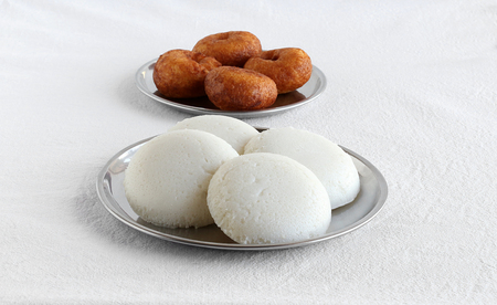 Idly or idli, is a healthy south Indian, vegetarian, steam-cooked food, is traditional and popular and is made from rice and lentil batter, and vada in the background, on steel plates.