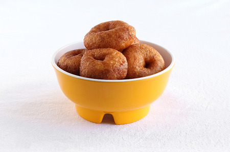 Medu vada or urud vada, south Indian, traditional, popular and vegetarian food, is usually eaten with idli or idly, in a bowl.