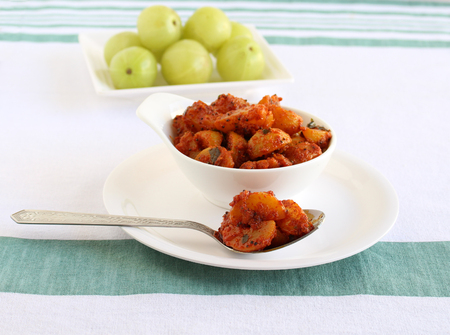 Indian gooseberry pickle on a spoon. This berry makes the pickle a healthy vegetarian side dish. 版權商用圖片