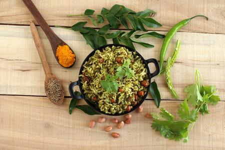 Arroz con hojas de curry, un plato vegetariano casero y saludable del sur de la India en un wok y algunos de los ingredientes principales de esta deliciosa preparación de arroz.