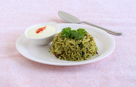 Curry leaves rice, a healthy, south Indian and home cooked vegetarian dish with yogurt topped with chili powder as a side dish.