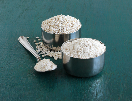 Barley flour, which is an ingredient in food items like bread and muffins, and pearl barley in a steel bowl and spoon and in the background is a bowl of barley grains.