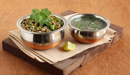 Moong or mung curry and rasam, which are home cooked and healthy Indian vegetarian food, in steel bowls. Imagens