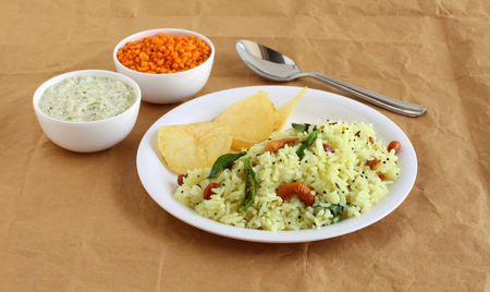 Lemon rice, a traditional, popular, and homemade south Indian vegetarian breakfast on a plate with potato chips, and coconut chutney as a side dish. Imagens
