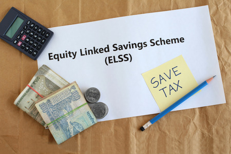 Equity linked savings scheme, elss, an Indian tax saving investment option, concept highlighted through text, Indian rupees and coins, a calculator and handwritten note. Imagens