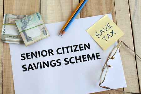 Senior citizen savings scheme concept highlighted through text on paper, Indian rupees and coins, a save-tax note, pencils and spectacles on a wooden background. Imagens