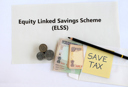 Equity linked savings scheme, elss, an Indian tax saving investment option, concept highlighted through text, Indian rupees in an envelope, coins and handwritten save-tax note. Imagens