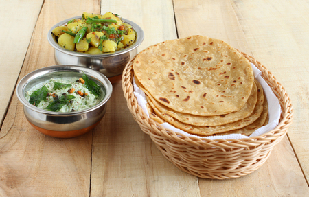 Chapati or Indian flat bread, which is a traditional and popular vegetarian breakfast or lunch item, with potato and onion curry and coconut chutney as side dishes.