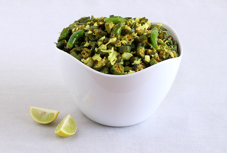 Bhindi curry, an Indian, delicious, and vegetarian cuisine made from okra, is a side dish for items like chapati and roti, in a bowl. Imagens
